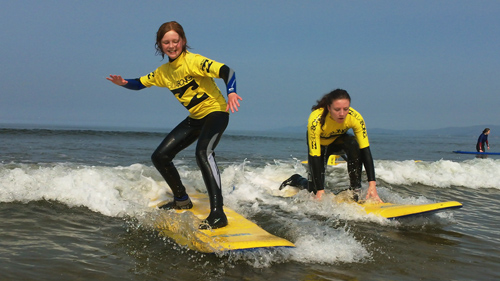 A photo of two teenagers surfing in shallow waters is visible
