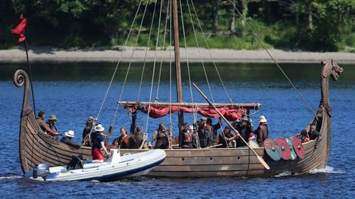 A boat is being filmed on a lake as part of a movie production