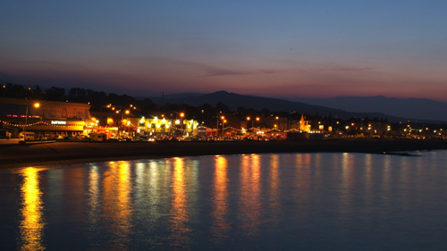 A picture from distance of a harbor late at night with lights shining on seafront