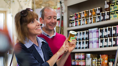 A couple are seen shopping where they are searching through a collection of different flavours of jam