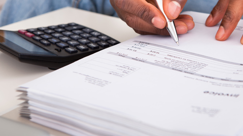 Photo of a man working on invoices