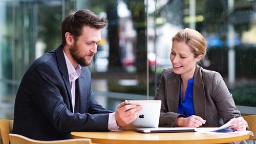 A man and a woman are discussing a visual from a tablet device at a desk