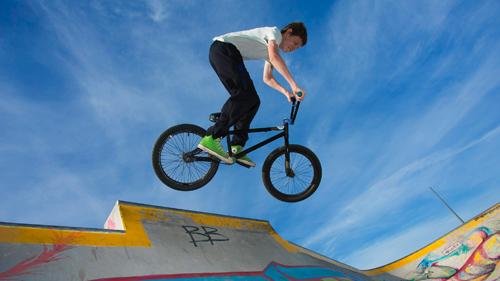 A boy is cycling high above a skateboard ramp