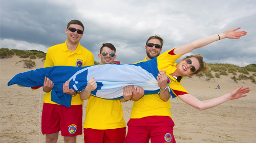 Three male lifeguards holding a female lifeguard in a staged pose for a photographer