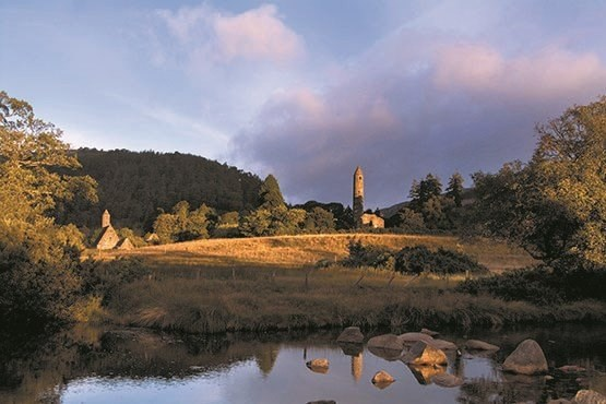 Glendalough round tower from across the lake